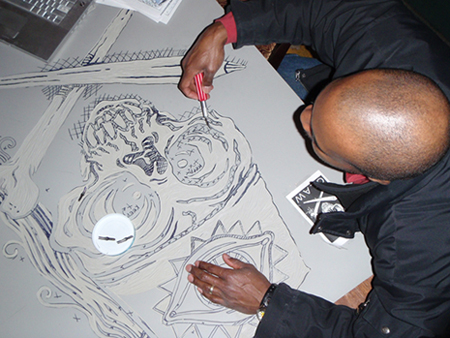 Stan Shaw carves on the poster block